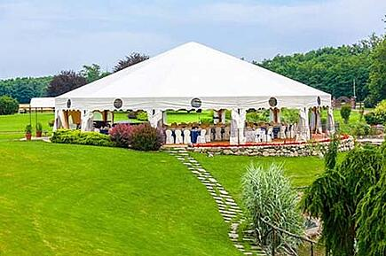 A large wedding tent that has been set up on a field